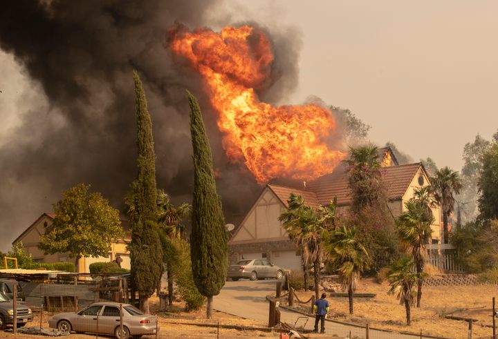 A man trying to save a home in Vacaville, California, on Wednesday watches futilely as it goes up in flames.