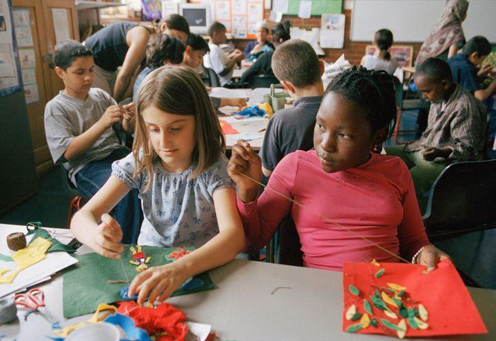 Childrenlearning to sew at Millfields Community School in London, U.K.