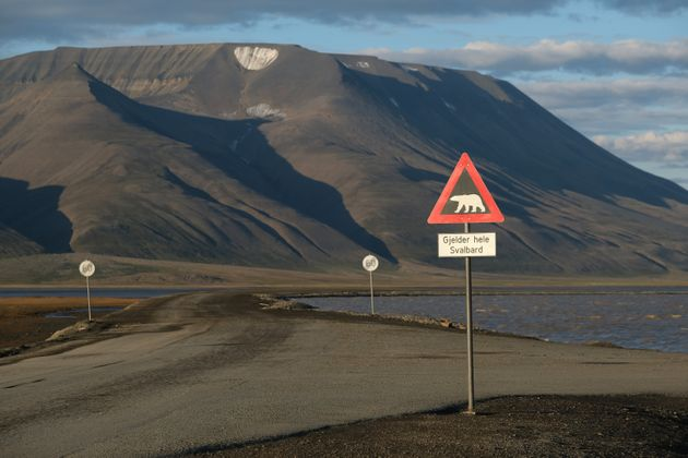 Mountains nearly devoid of snow stand behind a road and a polar bear warning sign during a summer heatwave...