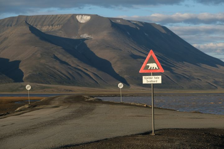 Mountains nearly devoid of snow stand behind a road and a polar bear warning sign during a summer heatwave on Svalbard archip