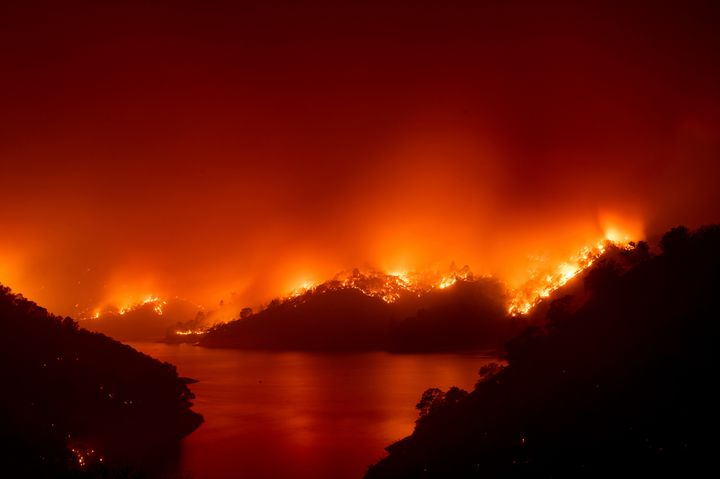Flames from the wildfire designated as the LNU Lightning Complex are seen around Lake Berryessa in Napa County, California on Wednesday. Fire crews across the region have scrambled to contain dozens of wildfires sparked by lightning strikes.