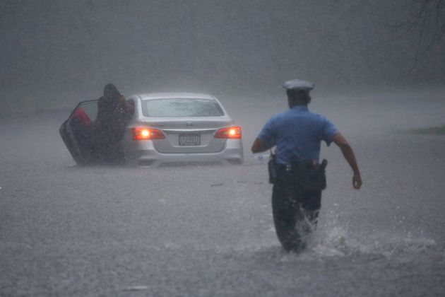 A Philadelphia police officer rushes to help a stranded motorist during Tropical Storm Isaias on Aug....