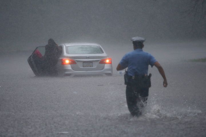 A Philadelphia police officer rushes to help a stranded motorist during Tropical Storm Isaias on Aug. 4. The storm spawned to