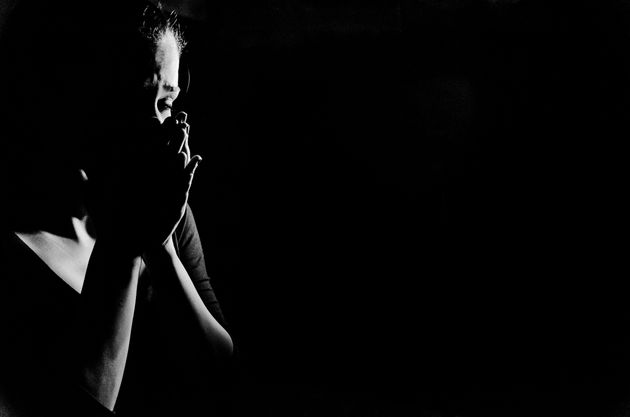 Young woman stanging in the dark crying,she is feeling hopless