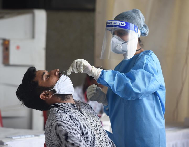 A health worker takes samples for Covid-19 rapid antigen tests at a testing facility at Anand Vihar Bus Terminal on August 17, 2020 in New Delhi.