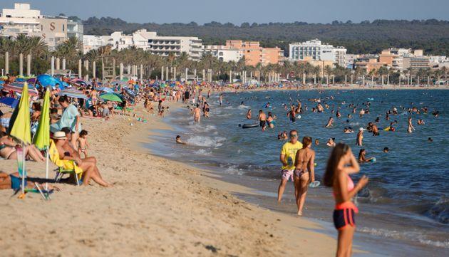 People enjoy the beach in Palma de Mallorca, Spain, on July