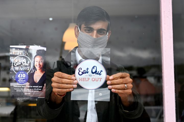 U.K. Chancellor of the Exchequer Rishi Sunak places an Eat Out to Help Out sticker in the window of a business. The government has spent millions of pounds on the program, which subsidizes the cost of restaurant meals.
