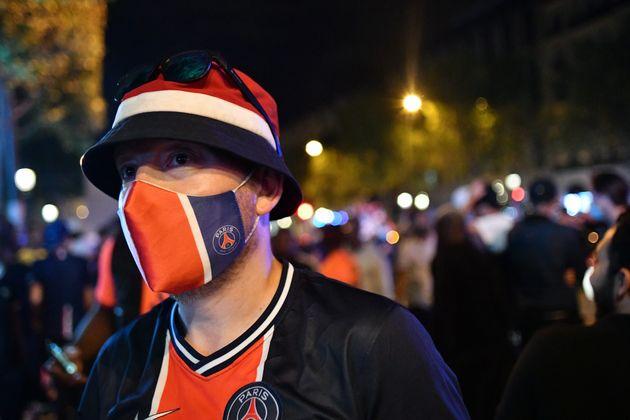 Un fan du PSG célébrant la qualification en finale sur les Champs-Elysées