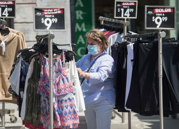 A woman wears a face mask as she shops in Montreal on Aug. 15, 2020.Retail sales soared 23.7 per...