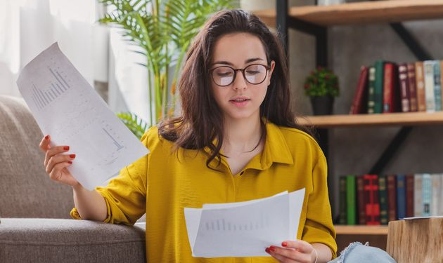 Young woman looking at bills while sitting on floor at living room managing home