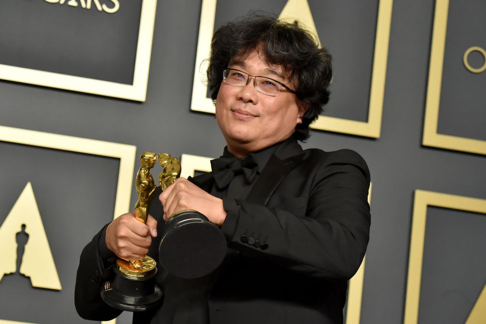 """Bong Joon Ho with two of his Oscars for """"Parasite"""" at the 2020 Academy Awards."""