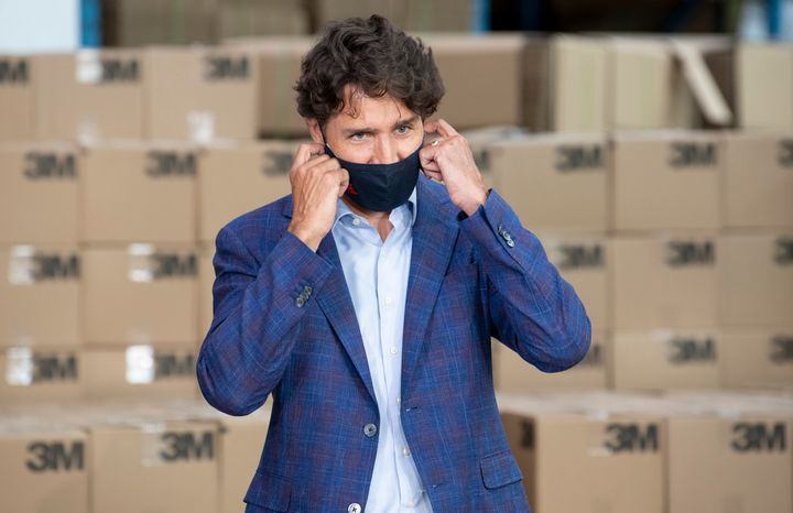 Prime Minister Justin Trudeau removes a cloth mask as he approaches the podium during an announcement at a factory in Brockville, Ont., on Aug. 21, 2020.