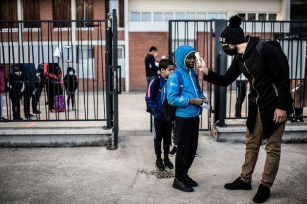 Alunos passam por medição de temperatura antes de entrar na escola Saint-Exupery em La Courneuve, subúrbio...