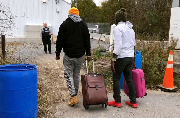 In this Nov. 4, 2019, photo, two men from Nigeria illegally cross the U.S. border at Roxham Road in Champlain,...
