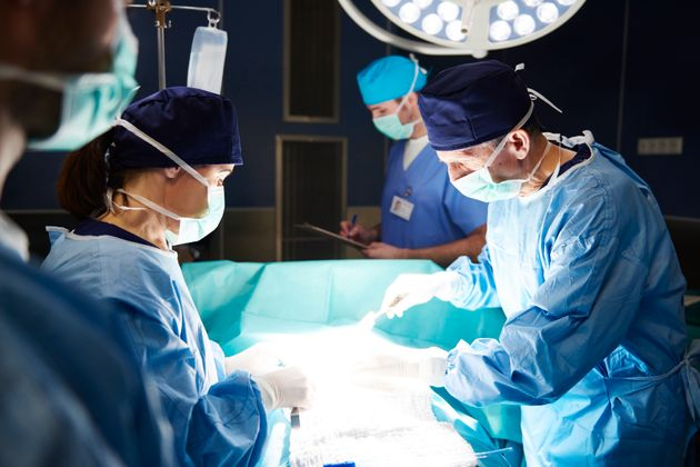 Team of busy surgeons over the operating