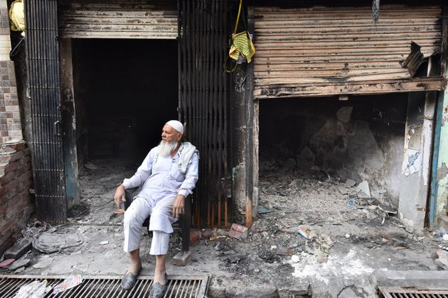 An elderly man seated outside shops burnt in the riots across North East Delhi, at Shiv Vihar, on March...