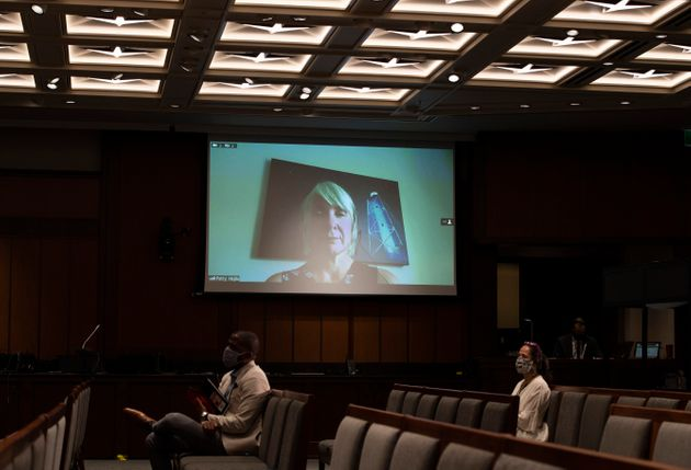 Minister of Health Patty Hajdu is seen on a videoconference display above journalists during a news conference...