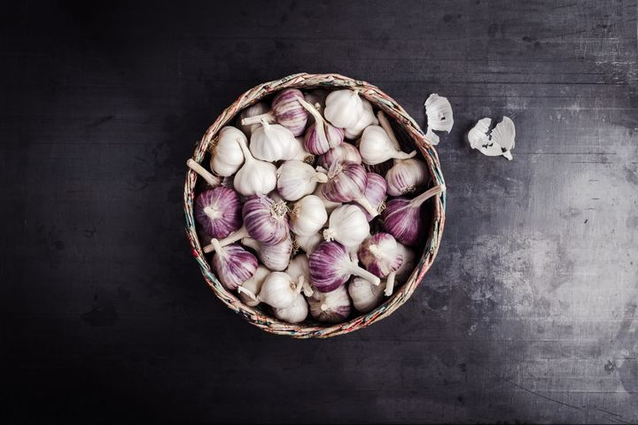 Fresh purple garlic in handmade basket made from post consumer waste newsprint papers, top view