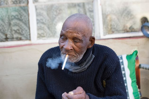 Fredie Blom enjoys a cigarette as he celebrates his 116th birthday at his home in Delft, near Cape Town,...