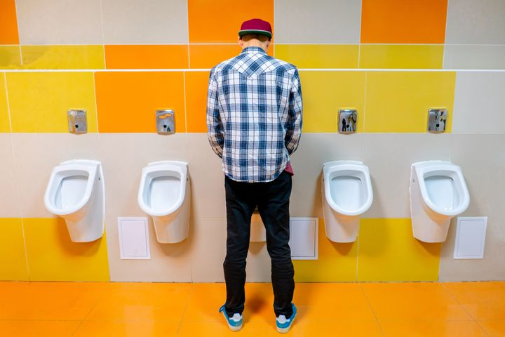 young man in the public toilet, standing next to the urinal in the trade center