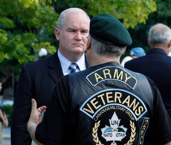 Erin O'Toole speaks with a veteran after taking part in the National Peacekeepers' Day ceremony in Ottawa on Aug. 9, 2015.