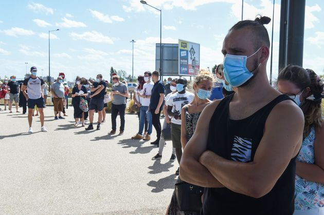 People queue wearing face mask at a COVID-19 test centre, at Parc Manceau, in Le Mans, north-western...