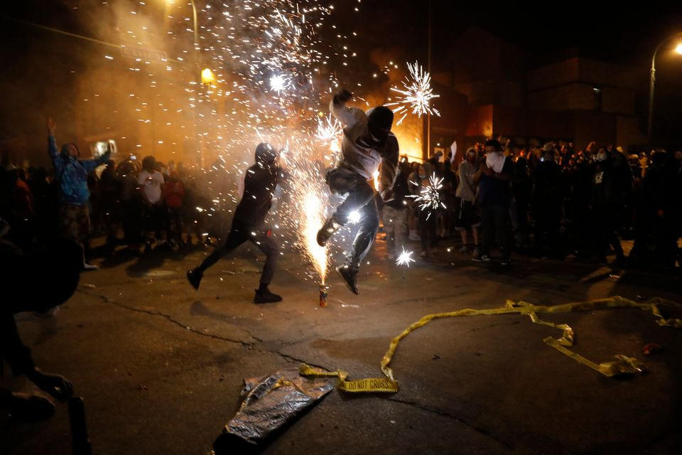 Protesters set off fireworks as a fire burns at the Minneapolis police 3rd Precinct building, May 28,...