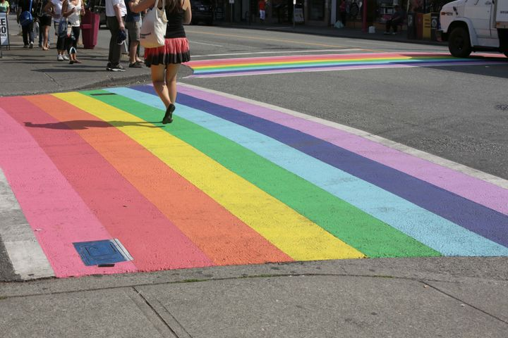 A pedestrian crosses the rainbow crosswalk at the intersection of Davie and Bute Streets in Vancouver's west end.