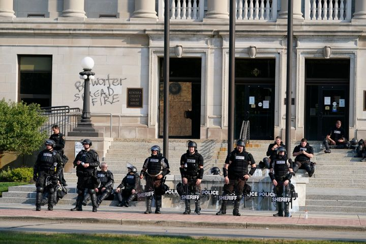 Police in riot gear stand outside the Kenosha County Court House on Monday following overnight protests over the shooting of