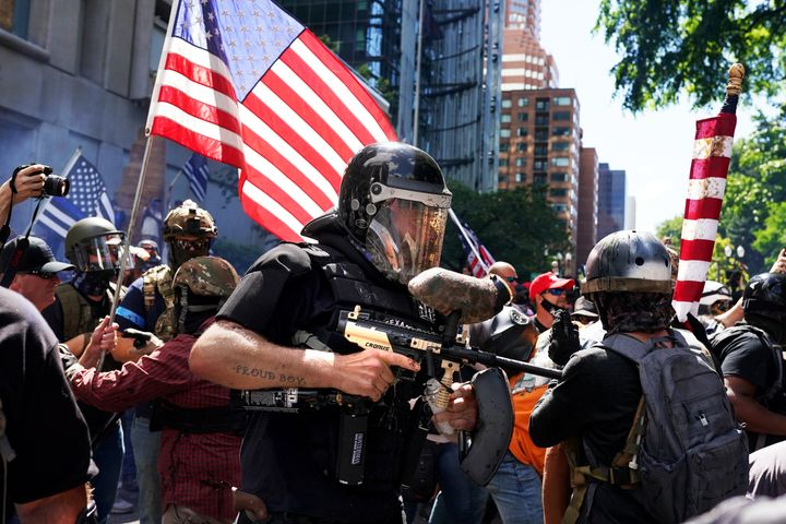 A member of the Proud Boys fires a paintball gun into a crowd of protesters against police brutality as the two sides clashed