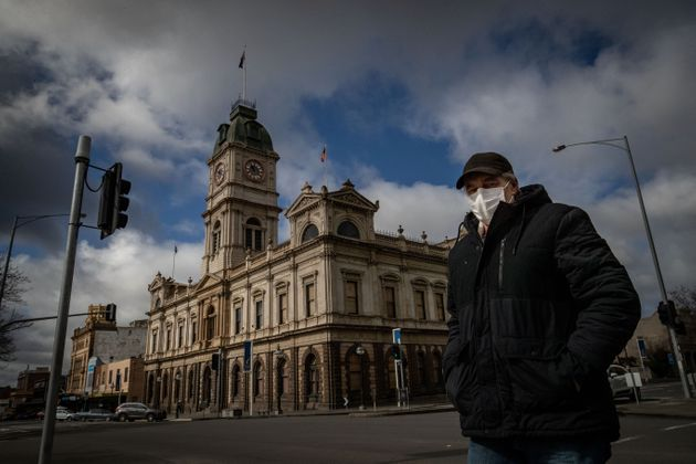 A man wearing a mask walks across Sturt Street in Ballarat on August 21, 2020 in Ballarat, Australia....