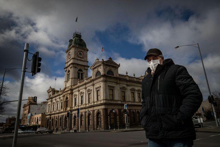A man wearing a mask walks across Sturt Street in Ballarat on August 21, 2020 in Ballarat, Australia. COVID-19 testing in Ballarat has increased as health authorities work to avoid the spread of coronavirus in regional Victoria.