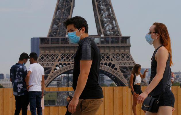 People wearing masks to prevent the spread of coronavirus walk at Trocadero plaza near Eiffel Tower in...