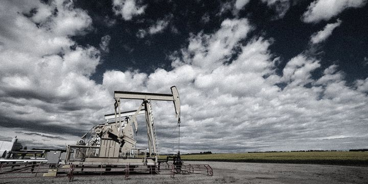 Pump jacks draw oil out of the ground near a canola field in Olds, Alta., on July 16, 2020.