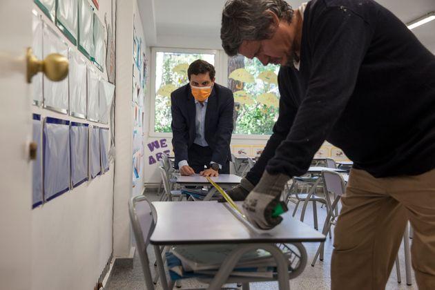 Dos trabajadores preparan las instalaciones de un colegio en