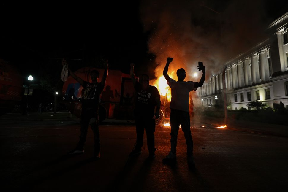 Protesters in response to the police shooting of Jacob Blake light a cleaning truck on fire in Kenosha, Wisconsin, on Aug. 24