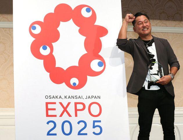 決定した2025年大阪・関西万博のロゴマーク。右は最優秀作品に選ばれた「TEAM INARI(チームイナリ)」代表のシマダタモツさん=25日午後、大阪市北区