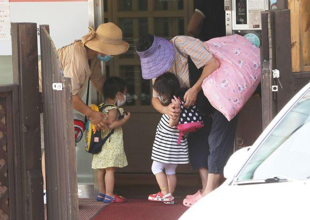 신종 코로나바이러스 감염증(코로나19) 재확산으로 사회적 거리두기가 2단계로 격상된 가운데 25일 서울 종로구의 한 국공립어린이집에서 할머니들이 자녀를 긴급돌봄교실에 등원 시키고