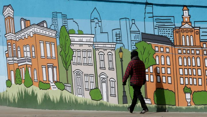 A pedestrian walks past a mural showing the skyline and several landmark buildings of Cincinnati. The city faces a housing sh