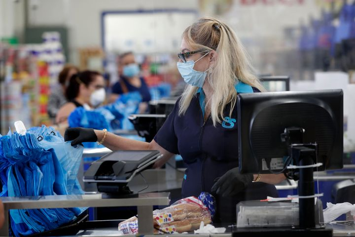 Cashier Mercedes Peña wears a protective mask as she works behind a plastic shield at the Presidente Supermarket this