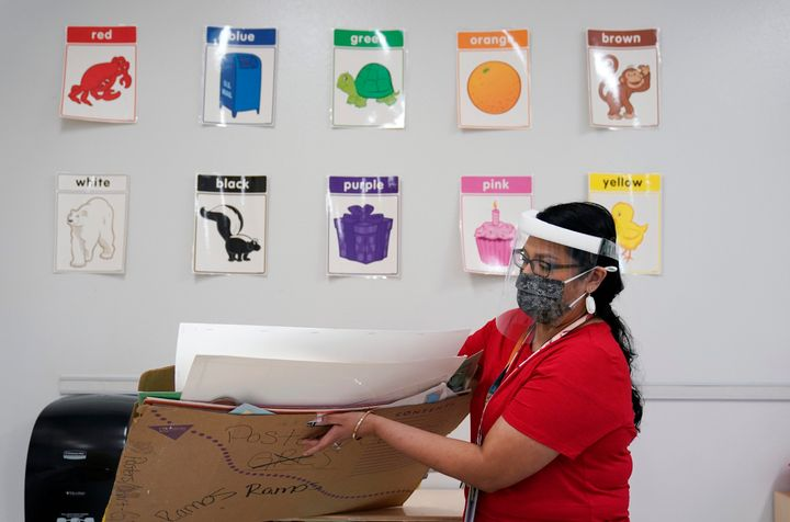Wearing a face mask and shield to protect against the spread of COVID-19, kindergarten teacher Judith Ramos prepares her clas