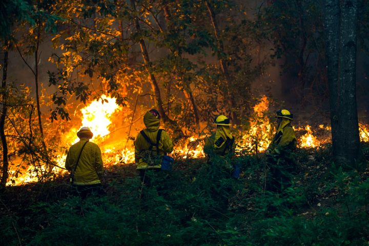 Firefighters battling a blaze near a house during the CZU Lightning complex fire in Boulder Creek, California, on Sunday.