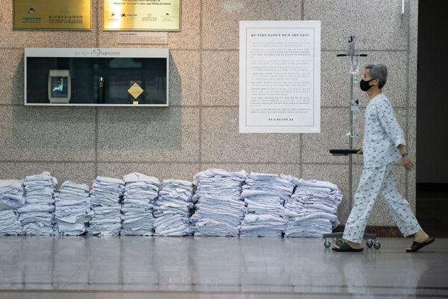 (자료사진) 서울 송파구 서울아산병원 로비에 전공의들이 벗어놓은 의사 가운 앞으로 한 환자가 지나가고 있다. 전공의들은 이날부터 무기한 파업에 들어갔다.