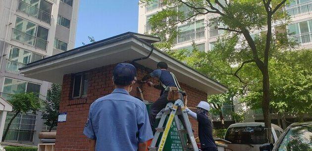 지난 25일 설비업체 직원들이 대전 대덕구 한 아파트 경비실에 미니태양광 시설을 설치하는 모습을 이 아파트 경비원이 바라보고