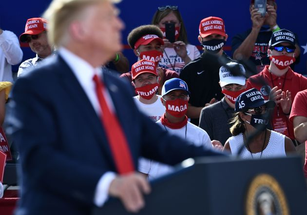 Americans wear face masks during a speech by U.S. President Donald Trump on Aug. 17 in Oshkosh,