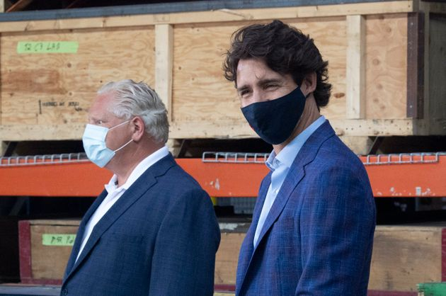 Prime Minister Justin Trudeau smiles with a face mask on standing beside Ontario Premier Doug Ford during...