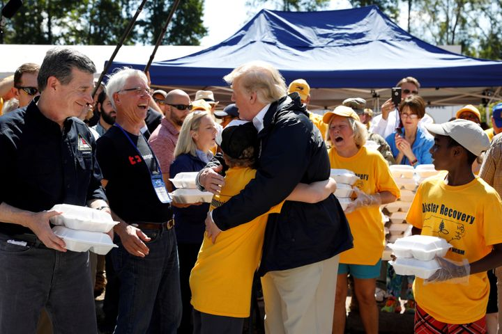 President Donald Trump embraces a boy at a distribution center in New Bern, North Carolina, while participating in a tour of