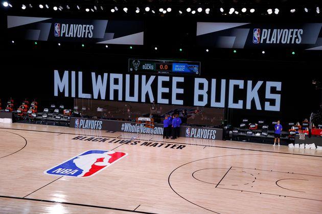 Los árbitros se apiñan en una cancha vacía durante el juego programado de Milwaukee Bucks y Orlando Magic el ...