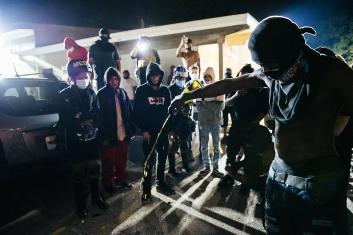 A man pours out an alcoholic beverage where an anti-racism protester was killed in Kenosha, Wisconsin, this week.