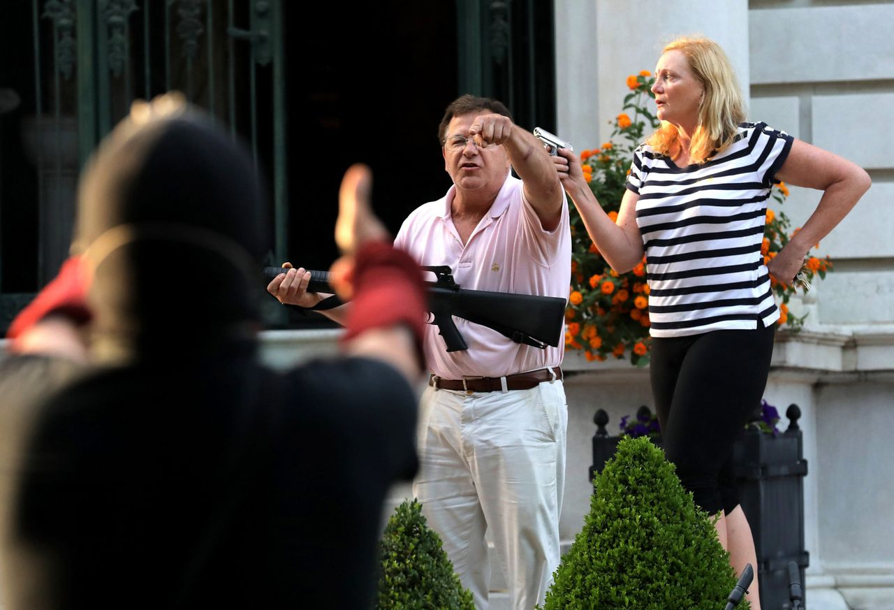 Mark and Patricia McCloskey standing outside their home in St. Louis in June, confronting Black Lives Matter protesters with guns. They were featured speakers at the Republican National Convention this week.